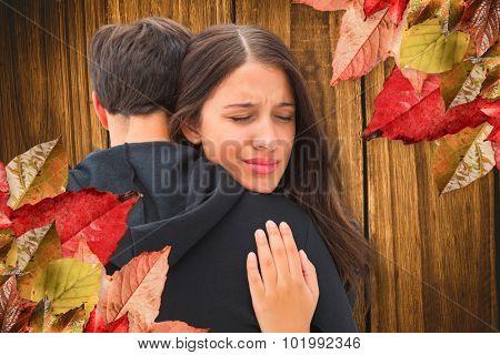 Unhappy brunette hugging her boyfriend against wooden table