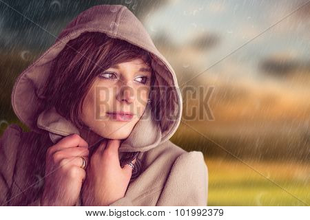 Beautiful woman wearing winter coat looking away against country scene