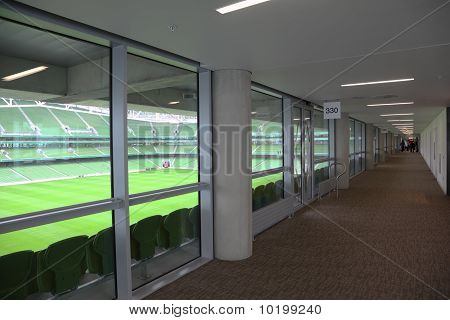 Corridor and rows of green folding seats in a big empty stadium.