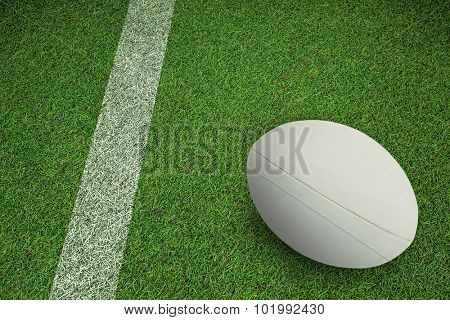 Close-up of rugby ball against pitch with line
