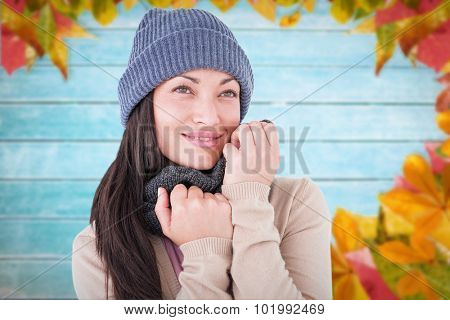 Attractive brunette looking up wearing warm clothes against autumn leaves on wood
