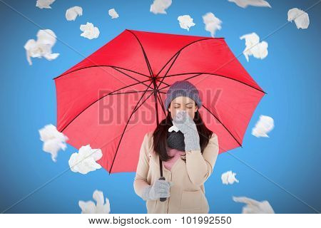 Sick brunette blowing her nose while holding an umbrella against blue background with vignette