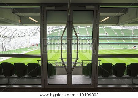 Door and rows of green folding seats in a big empty stadium.