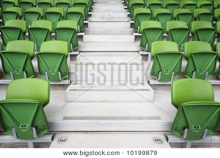 Rows of folded green plastic seats in very big empty stadium