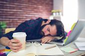 Tired creative editor holding disposable cup while sleeping on office desk poster