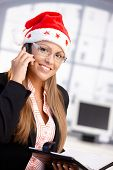 Pretty Female Wearing Santa Hat Smiling In Office
