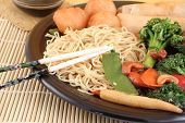 stock photo of lo mein  - delicious chinese lo mein noodles and stir fry vegetables with cashews with chicken balls spring rolls soya sauce and chopsticks on a bamboo placemat - JPG