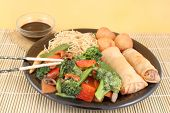 pic of lo mein  - delicious chinese lo mein noodles and stir fry vegetables with cashews with chicken balls spring rolls soya sauce and chopsticks on a bamboo placemat - JPG