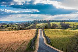 image of maryland  - paved road going through the center of an autumn landscape of the Antietam Battlefield near Sharpsburg - JPG