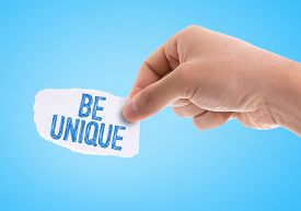 image of uniqueness  - Piece of paper with the word Be Unique with blue background - JPG