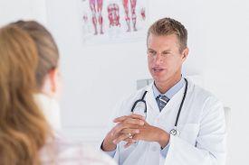 stock photo of neck brace  - Doctor talking to patient wearing neck brace in medical office - JPG