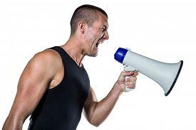 foto of irritated  - Irritated male trainer yelling through megaphone against white background - JPG