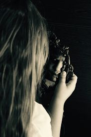 pic of horrifying  - a girl staring at the mirror but her reflection is horrifying.