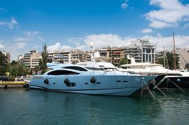 stock photo of piraeus  - Fast and luxury yacht under a heavy cloudscape at marina Zeas Piraeus Greece - JPG