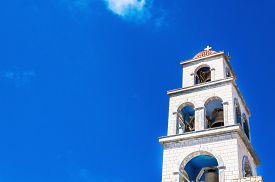 picture of blue-bell  - View on church tower with bell made from white stones over clear blue sky - JPG