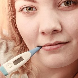 foto of high fever  - Sick ill woman with digital thermometer in mouth - JPG