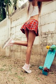 pic of mini-skirt  - Close up of a young lady with sporty butt in a red tartan mini skirt with blue penny skateboard trying to climb over the fence of a tropical garden - JPG