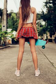 stock photo of mini-skirt  - Skinny young lady with fit ass in a sexy red tartan mini skirt with blue penny skateboard shortboard stands on the tropical street - JPG