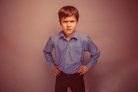 pic of frown  - portrait of a teenage boy frowning brown hair of European appearance on a gray background retro - JPG