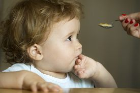 stock photo of frown  - Sad frown serious cute charming little boy child with brown hair and hazel eyes looking at spoon holding by mother hand and cover mouth by his palm on grey background indoor horizontal picture - JPG