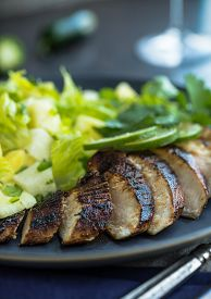 stock photo of jerks  - Spicy jerk chicken with lime and green salad with cilantro  - JPG