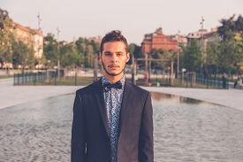 pic of bow tie hair  - Young handsome man with short hair wearing a bow tie and posing in the city streets - JPG