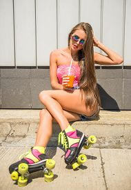 picture of roller-derby  - Beautiful young woman is posing outdoor in rollers with juice - JPG