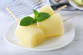 foto of lolli  - Melon ice lolly on wooden table - JPG