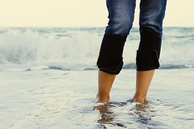 image of wet pants  - Female legs in jeans standing in the sea water on the background of a breaking wave - JPG
