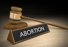 picture of pro-life  - A wooden court gavel next to a sign that says abortion on it - JPG