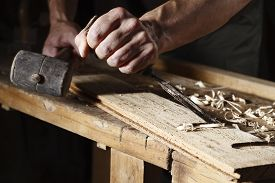 image of chisel  - Closeup of a carpenter hands working with a chisel and hammer on wooden workbench - JPG