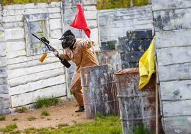 picture of paintball  - Armed man setting up victory flag in paintball mission - JPG