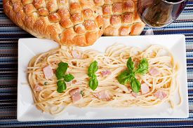 stock photo of carbonara  - Spaghetti carbonara decorated with fresh basil leaves with ciabatta bread and a glass of red wine - JPG