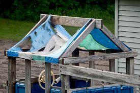 stock photo of tarp  - Play house tarp roof ruined by weather - JPG