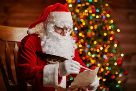 stock photo of letters to santa claus  - Santa Claus answering Christmas letter by sparkling firtree - JPG