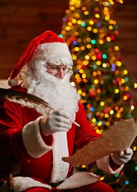 foto of letters to santa claus  - Santa Claus with feather answering Christmas letter - JPG