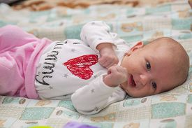 stock photo of papule  - The baby is lying on the bed - JPG