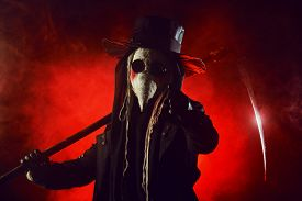 stock photo of scythe  - Portrait of a terrible plague doctor with a scythe - JPG