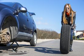 picture of biker  - Female biker rolls big wheel Young female - JPG