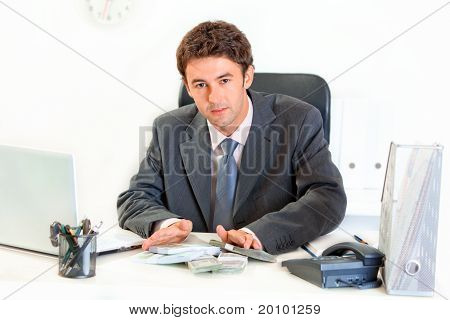 Modern businessman sitting at office desk and giving money packs