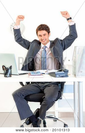 Excited modern businessman sitting at office desk and rejoicing his success