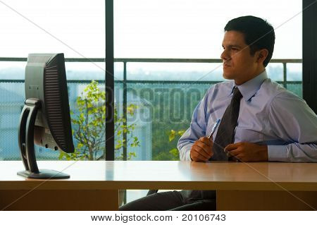 Hispanic Male Executive Office Looking Monitor
