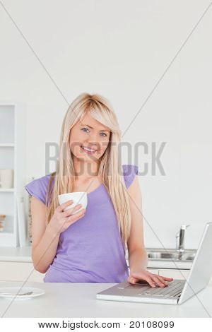 Attractive Blonde Woman Holding A Cup Of Coffee And Relaxing On A Laptop In The Kitchen