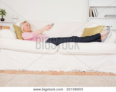 Attractive Blonde Woman Watching Tv While Lying On A Sofa