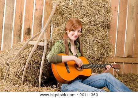 Young Country Woman  Play Guitar In Barn