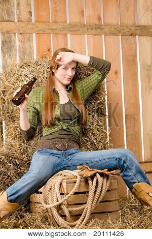 Provocative Young Cowgirl Drink Beer In Barn