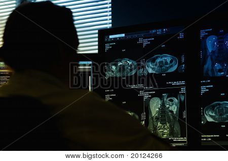Doctor Working At Computer Looking At Mri Scan