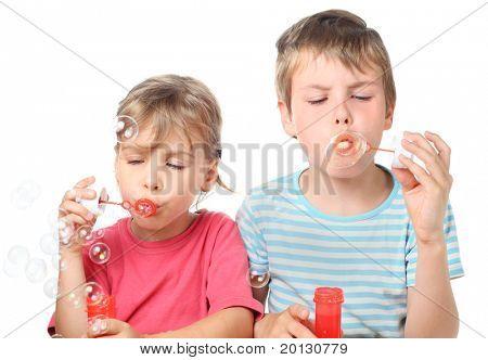 menino e menina sentada e soprando bolhas isoladas no branco