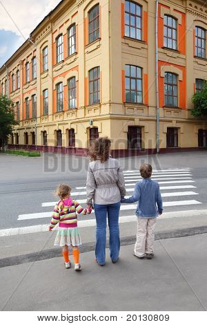 young mother holds hand of little daughter and son and crossing road, behind, yellow house, trees