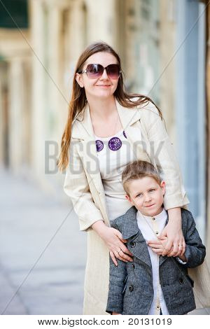 Mother and son outdoors in city on sunny spring day